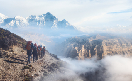 Group of tourists with backpacks descends down mountain trail during a hike in the Upper Mustang, Nepal. Beautiful inspirational landscape, trekking and activity. Stock Photo