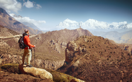 Hiker with backpack looks at the beautiful mountains in Upper Mustang, Annapurna conservation area, Trekking route, Himalaya. Beautiful inspirational landscape, trekking and activity. Travel sport lifestyle concept