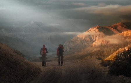 Two travelers with backpacks go high in the mountains of the Upper Mustang, Nepal. Traveling along the mountains, freedom and active lifestyle concept. Stock Photo