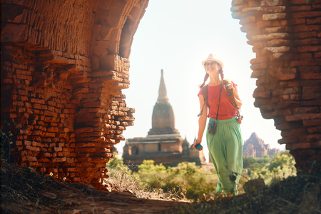 Positive emotions. Happy woman traveler with a backpack walking through the Old Bagan looking the ancient Buddhist stupas. Myanmar. Concept of travel and adventure in Asia. Stock Photo