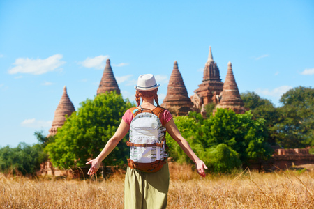 Rear view of woman traveler with a backpack walking through the field to the ancient Buddhist stupas in Old Bagan, Myanmar. Concept of travel and adventure in Asia. Stock Photo