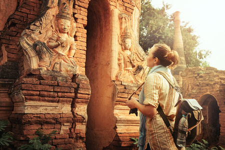 Woman tourist enjoying view a looking at Buddhist stupas in famous ancient Indein. Burma, Asia.  Traveling along Asia, active lifestyle concept.