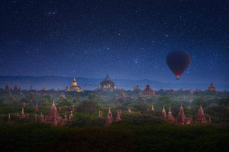 Early morning in Old Bagan with overflying balloon over the ancient temples in the background of the starry sky. Myanmar (Burma) Banque d'images - 122696527