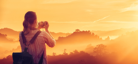 Woman traveler with backpack enjoying sunrise views in rainforest. Myanmar, Asia. Panoramic view. Traveling along Asia, active and adventure lifestyle concept.