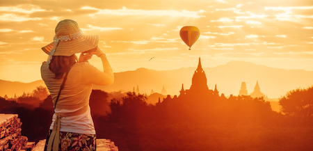 Woman traveler in hat enjoying sunset views of Buddhist stupas in the ancient Bagan. Myanmar, Asia.  Panoramic view. Traveling along Asia, active and adventure lifestyle concept.