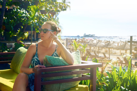 Woman relaxing outdoors on a summer sunny day in a luxury hotel on the coast of the resort of Ngapali, Myanmar. Traveling along Asia, holiday and beach. Stock Photo