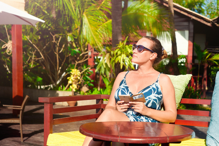 Woman relaxing outdoors on a summer sunny day in a luxury hotel on the coast of the resort of Ngapali, Myanmar. Summer holiday and youth lifestyle concept
