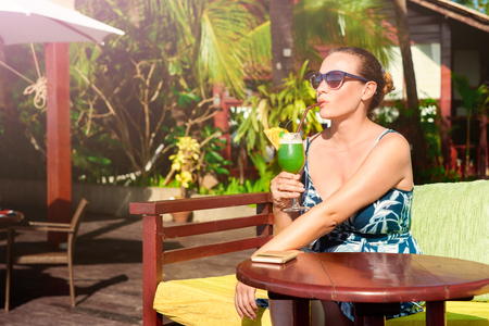 Attractive woman enjoying a tropical cocktail on vacation on a background of luxurious bungalows. Banque d'images - 122696533