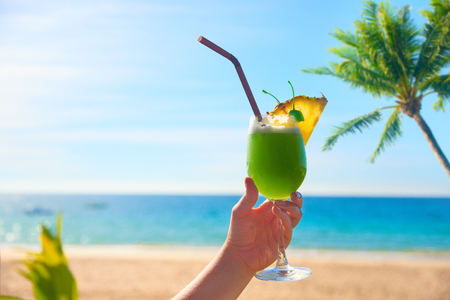 Cheers vacation! Taking exotic tropical cocktail in hand. Summer landscape on sunny day is on the background.  Stock Photo