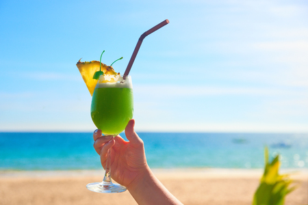 Cheers vacation! Taking exotic tropical cocktail in hand. Summer landscape on sunny day is on the background. Banque d'images - 122696536