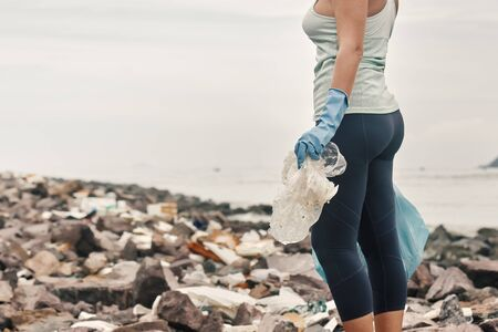 Woman volunteer helps clean the coastline of plastic garbage. Earth day and environmental improvement concept.