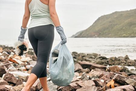 Woman volunteer in gloves holds plastic garbage on the background of sea coast.Earth day and environmental improvement concept Banco de Imagens