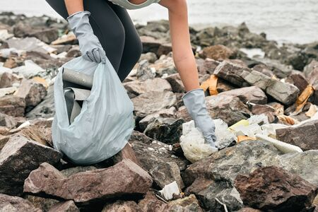 Close Up woman hand picking up garbage plastic for cleaning to sea coast. Earth day and environmental improvement concept.