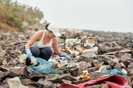 Woman helps clean the coastline of plastic garbage. Earth day and environmental improvement concept.