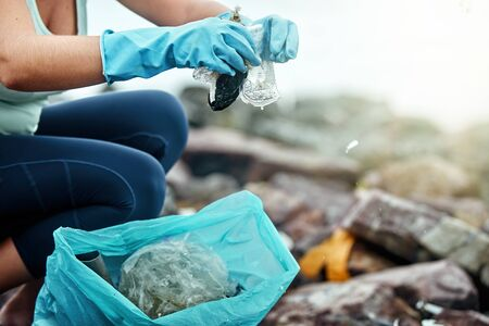 Closeup of a female gloved hand picking up plastic trash in a bag.Earth day and environmental improvement concept. Focus on hand on garbage and gloves.