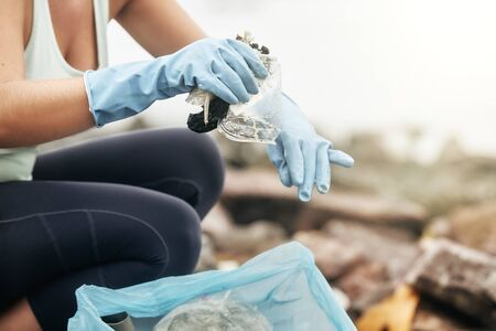 Closeup of a female gloved hand picking up plastic trash in a bag.