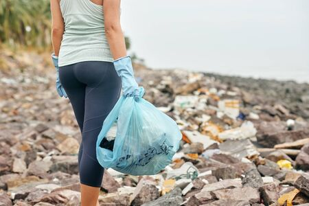 Female hand in gloves holds plastic garbage on the background of dirty coast. Earth day and environmental improvement concept.