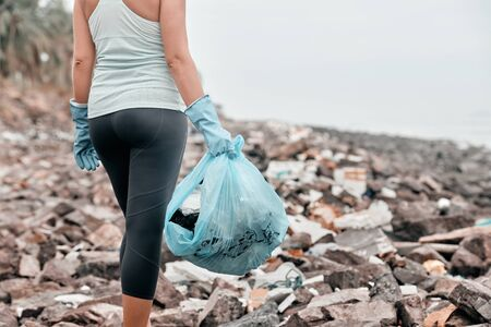 Closeup of a female gloved hand picking up plastic trash in a bag.Earth day and environmental improvement concept.