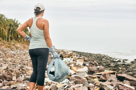 Woman volunteer in gloves holds plastic garbage on the background of sea coast. Focus on gloved hand. Earth day and environmental improvement concept.