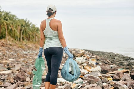 Young woman volunteer in gloves holds plastic garbage on the background of sea coast. Focus on gloved hand. Earth day and environmental improvement concept.
