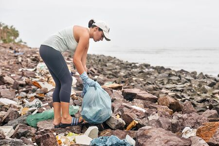 Woman in gloves collects plastic trash on the background of dirty coast.