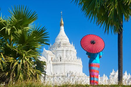 A young woman in traditional dress with an umbrella is looking at the Hsinbyume-Paya pagoda near the old town of Mandalay, Myanmar.