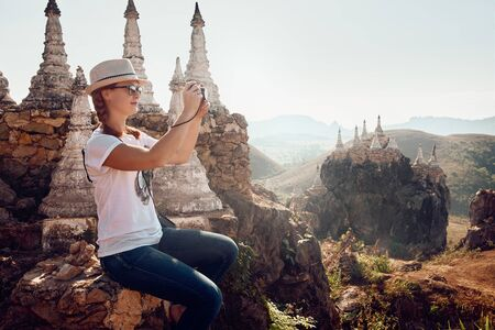 young woman traveller photographs landscape and stupas in the temple complex Main May' Tha-Khin-Ma Mountain. Myanmar(Burma), Asia. Traveling along Asia, travel and adventure lifestyle concept.