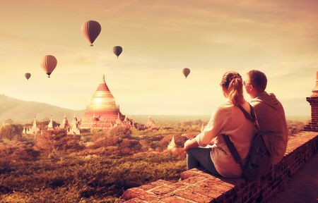 Happy tourists, friends, enjoy watching the flight of balloons over the old Bagan in Myanmar.Young people having fun traveling together. Travel, holiday, relationship and sport concept.