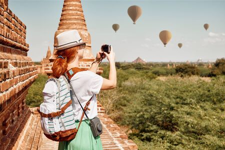 Young female traveler in hat enjoying views of Buddhist stupas in the ancient Bagan. Myanmar, Asia. Traveling along Asia, active and adventure lifestyle concept.