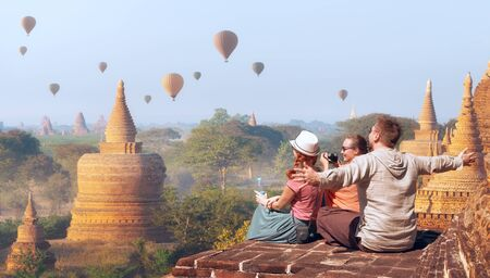 Happy tourists, friends, vacationers in the summer holidays in Old Bagan, Myanmar.Young people having fun traveling together. Travel, holiday, relationship and sport concept.