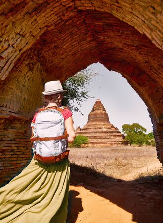 Happy woman traveler with a backpack walking through the Old Bagan looking the ancient Buddhist stupas. Myanmar. Concept of travel and adventure in Asia.  Banco de Imagens