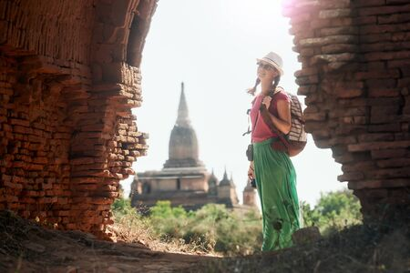 Positive emotions. Happy woman traveler with a backpack walking through the Old Bagan looking the ancient Buddhist ruins. Myanmar. Concept of travel and adventure in Asia. Banco de Imagens