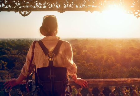 Young woman tourist with a backpack stands and watches the sunset over the forest on an old wooden balcony.