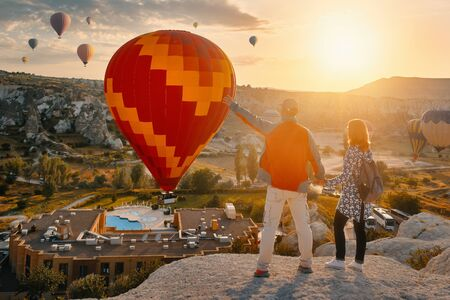 Couple travelers watches colorful balloons flying on an early sunny morning in Cappadocia.Turkey. Banco de Imagens