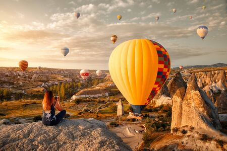 Young woman watches and photographs flying colorful balloons on an early morning in Goreme Valley, Cappadocia. Turkey