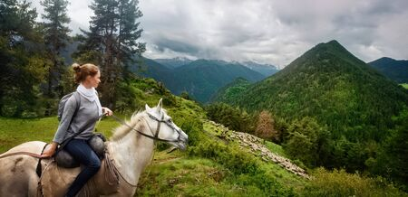 Young woman travels during summer vacation riding horse high in mountains and watches herd of sheep graze against background of beautiful mountains in the province of Tusheti, Georgia country .