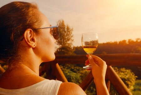 Happy woman with a glass enjoys a delicious drink while sitting on the terrace during sunset