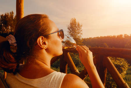 young woman with a glass enjoys a delicious drink while sitting on the terrace during sunset Banco de Imagens