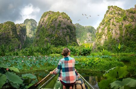 Woman traveling by boat on river amidst the scenic green karst mountains in Ninh Binh province, Vietnam Banco de Imagens