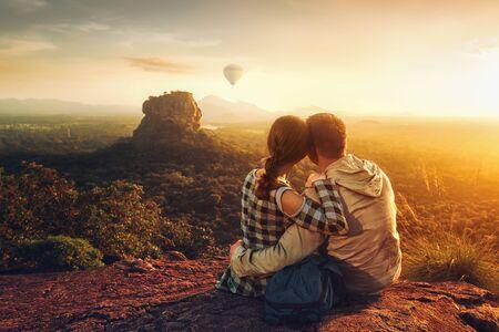 couple travelers watch beautiful sunset near famous rocky plateau Lion peak, Sigiriya. Sri Lanka