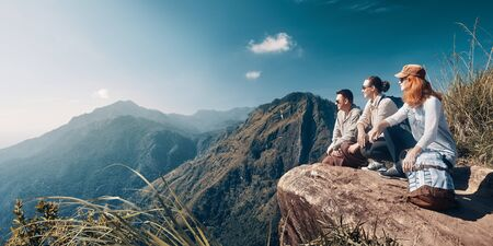 The company of young travelers look at the beautiful mountain peak