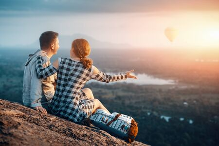 Happy couple enjoying the company of each other during a beautiful sunset sitting on Pidurangala Mountain, Sigiriya. Sri Lanka. Traveling in mountains, freedom and active lifestyle concept.
