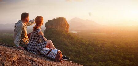 couple travelers watch a beautiful sunset near the famous rocky plateau Lion peak, Sigiriya. Sri Lanka