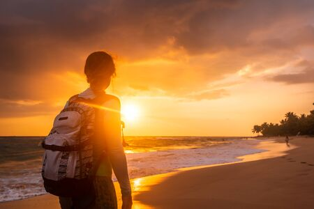 Girl with backpack during summer holidays is along the coast on background of beautiful sunset.