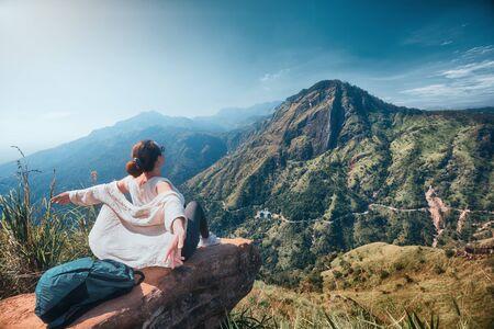 Woman traveler enjoying early morning beautiful nature on background of mountain peak