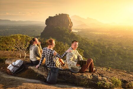 Group young tourists relaxes and watches during vacation colorful sunset on background of famous rocky plateau Lion peak, Sigiriya. Sri Lanka Banco de Imagens