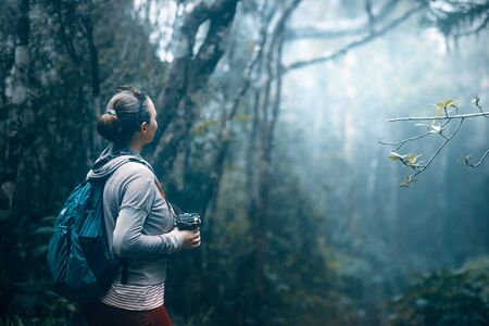 Woman with backpack and camera looking at the rain forest in the fog in the early morning.
