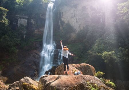 Young woman traveler is having fun on summer vacation on the background of Ramboda waterfall on the island of Sri Lanka. Concept travel in Asia, emotion and fun