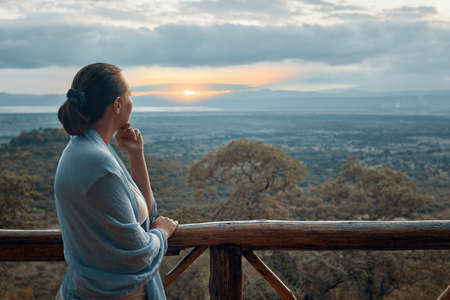 Woman alone on terrace watching sunset over mountains during summer vacation. Banco de Imagens