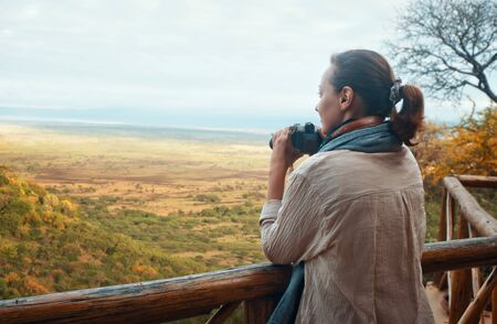 A young woman is standing on a wooden terrace with a camera looking at the African savannah in the early morning during summer vacation. Banco de Imagens